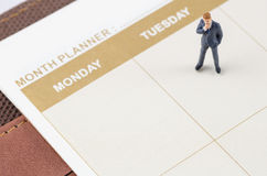 Businessman standing on the planner book. Miniature businessman standing on the planner book Stock Photo