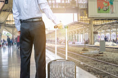 Businessman standing on the platform of a train station Stock Photos