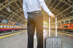 Businessman standing on the platform of a train station Stock Photo