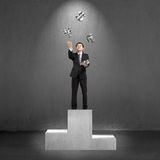 Businessman standing on podium throwing and catching 3D money sy Royalty Free Stock Photo