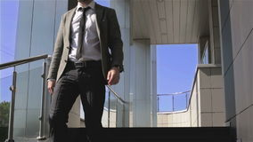 The businessman is standing on the porch of a business center looking at his watch and walking down the stairs. A man in a gray jacket and black tie stock footage