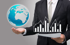 Businessman standing posture hand hold earth showing graph isola. Businessman standing posture hand hold earth showing graph  on gary background Stock Images