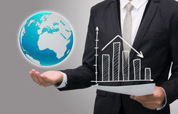 Businessman standing posture hand hold earth showing graph isola. Ted on gary background Stock Images