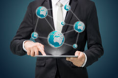 Businessman standing posture hand hold globe map on tablet Royalty Free Stock Image