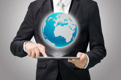 Businessman standing posture hand hold globe map on tablet Royalty Free Stock Photography