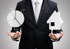 Businessman standing posture hand hold graph and house isolated Royalty Free Stock Photos
