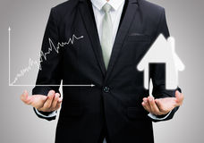 Businessman standing posture hand hold graph and house isolated Stock Photo