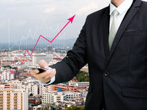 Businessman standing posture hand hold mobile phone analyze grap Stock Photography