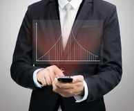 Businessman standing posture hand hold mobile phone analyze grap Royalty Free Stock Images