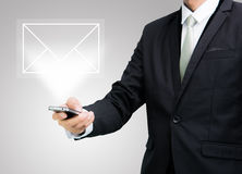 Businessman standing posture hand hold mobile phone send mail is Royalty Free Stock Images