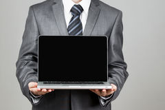 Businessman standing posture hand hold notebook laptop. On a grey baskground Stock Image