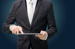 Businessman standing posture hand holding blank tablet. On dark background Royalty Free Stock Image