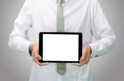 Businessman standing posture hand holding blank tablet isolated. On over gray background Royalty Free Stock Image