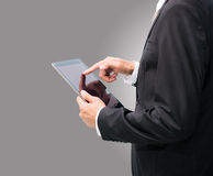Businessman standing posture hand holding blank tablet isolated. On over gray background Stock Images