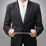 Businessman standing posture hand holding blank tablet. On over gray background Stock Photo