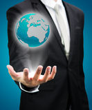 Businessman standing posture hand holding Earth icon isolated Royalty Free Stock Photography