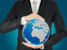 Businessman standing posture hand holding Earth icon isolated. On over blue background Royalty Free Stock Photography