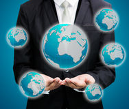 Businessman standing posture hand holding Earth icon isolated. On over blue background Royalty Free Stock Image