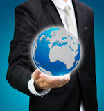 Businessman standing posture hand holding Earth icon isolated. On over blue background Stock Photo