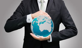 Businessman standing posture hand holding Earth icon isolated. On over blue background Royalty Free Stock Photo