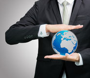 Businessman standing posture hand holding Earth icon isolated. On over gray background Stock Images