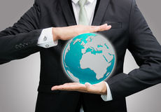 Businessman standing posture hand holding Earth icon isolated. On over gray background Stock Photography
