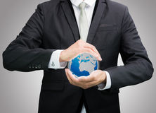 Businessman standing posture hand holding Earth icon  Stock Photography