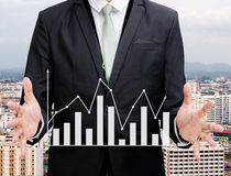 Businessman standing posture hand holding graph finance. On City background Stock Image