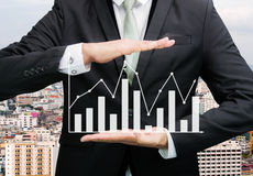 Businessman standing posture hand holding graph finance Stock Photo