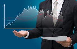 Businessman standing posture hand holding graph finance  Stock Image
