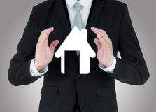 Businessman standing posture hand holding house icon isolated. On over blue background Royalty Free Stock Photography