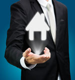 Businessman standing posture hand holding house icon isolated. On over blue background Royalty Free Stock Images