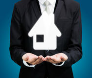 Businessman standing posture hand holding house icon isolated. On over blue background stock photography