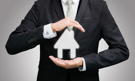 Businessman standing posture hand holding house icon isolated. On over blue background stock image