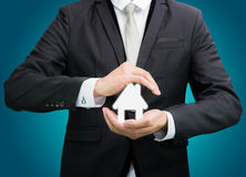 Businessman standing posture hand holding house icon isolated. On over blue background Stock Photo