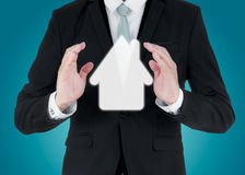 Businessman standing posture hand holding house icon isolated. On over blue background Royalty Free Stock Photos