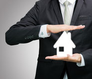 Businessman standing posture hand holding house icon isolated Stock Images