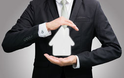 Businessman standing posture hand holding house icon. On over blue background stock image
