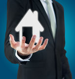 Businessman standing posture hand holding house icon. On over blue background stock photo
