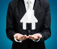 Businessman standing posture hand holding house icon. On over blue background stock images