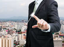 Businessman standing posture hand touch graph finance. On City background Royalty Free Stock Photography