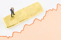 Businessman standing on the price chart with gold bar Stock Photography