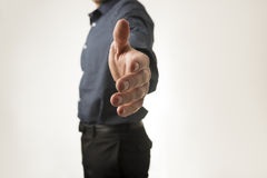 Businessman standing in profile offering you a handshake. Over white background Stock Image