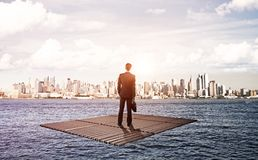 Businessman standing on raft Royalty Free Stock Image