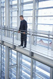 Businessman Standing By Railing In Modern Office Stock Photo