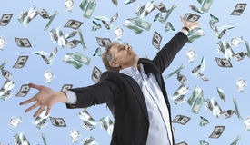Businessman standing in the rain of money. Dollar bills royalty free stock photography