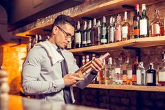 Businessman standing and reading description of wine. Reading description. Businessman standing at the bar stand and reading description of wine stock photography