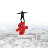 Businessman standing on red percentage sign balancing tightrope Stock Image