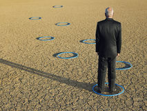 Businessman Standing In Ring At Barren Landscape. Rear view of middle aged businessman standing in ring at barren landscape Stock Image