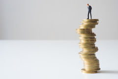 Businessman standing on risky coin stack. Stock Image